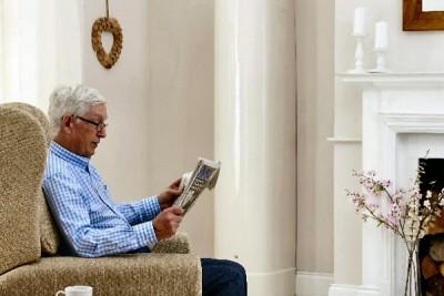 man in armchair reading magazine